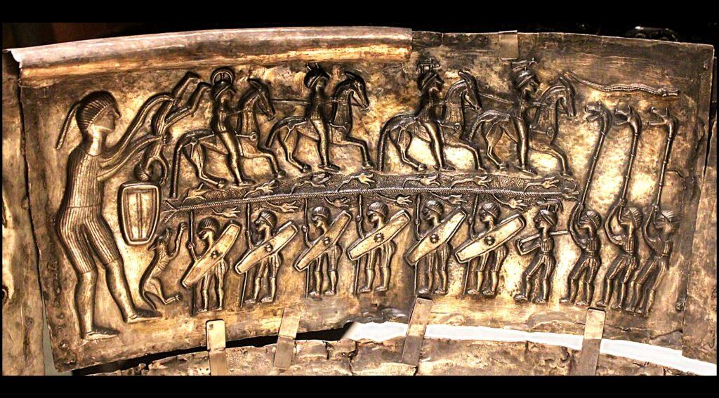 Eine Silberplatte, die zum Kessel von Gundestrup gehört, zeigt eine große Figur und viele kleine, die reiten, Schilder und andere Waffen tragen oder eine Carynx, eine Art Trompete, blasen.